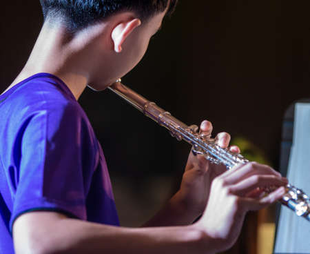 Back view of  a male musician student practicing playing flute at school Stock Photo
