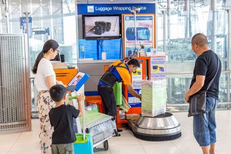 Bangkok, Thailand - 21 July 2018 - Luggage Wrapping Service staff wraps customer box while they wait at Suvarnabhumi International Airport in Bangkok, Thailand on July 21, 2018
