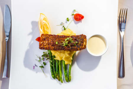 Grilled fish on top of mash potato and asparagus with cream souce on white plate