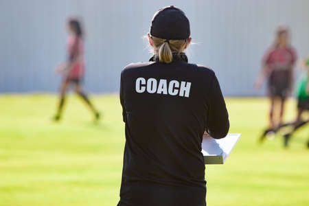 Back view of female sport coach in black COACH shirt at an outdoor sport field, watching her girl football team Stock Photo