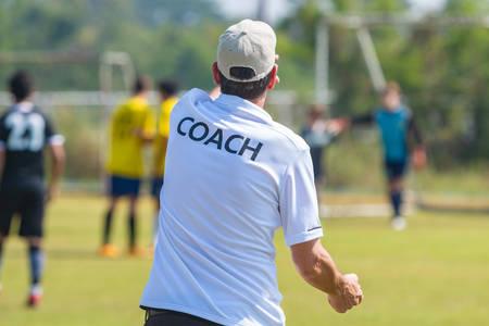 Achteraanzicht van mannelijke voetbalcoach in wit COACH-shirt op een buitenvoetbalveld dat richting geeft aan zijn voetbalteam