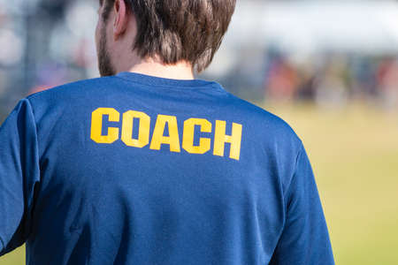 Back of male sport coach wearing blue shirt with yellow COACH word on back, at an outdoor sport field Stok Fotoğraf