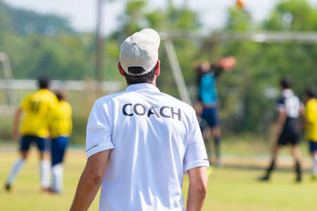 Back of football coach wearing white COACH shirt at an outdoor sport field coaching his team during a game, good for sport or coaching concept