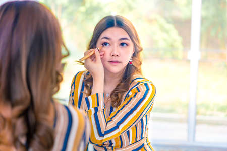 Beautiful young Asian woman putting on her make up in front of her larger bedroom window with the view of her garden in the background
