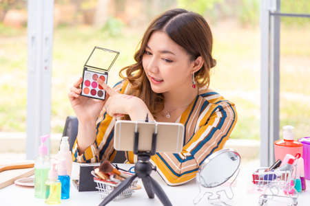 Beautiful young Asian woman, vlogger, holding and  reviewing beauty products on a video blog at home