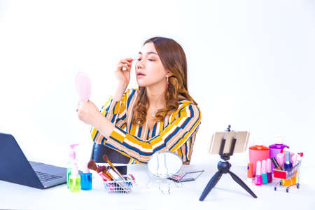 Beautiful young Asian vlogger woman putting her make up on to show online product review at home, modern small business concept