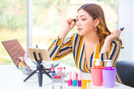 Beautiful young Asian woman putting her make up on during her online product review at home, online beauty cosmetic review concept Banco de Imagens