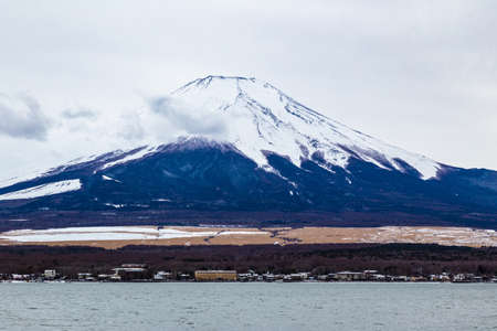 Moiunt Fuji standing tall against overcast white sky with some fluffy clouds floating in front
