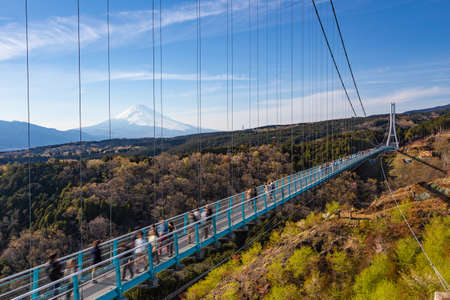People walkin on Mishima Skywalk bridge with Mount fuji seen in the distant, clear sunny day