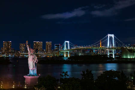 Odaiba Rainbow Bridge and Tokyo Tower seen in the distant against night sky and Statue of Liberty in the foreground Redactioneel
