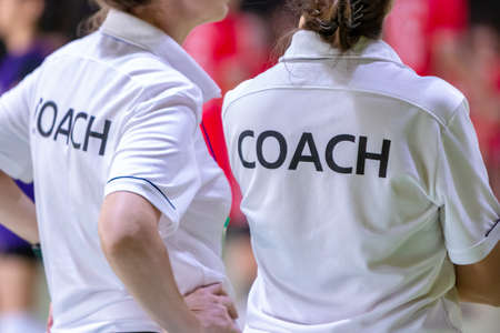 Female coaches in white COACH shirt at an indoor sport game Banco de Imagens