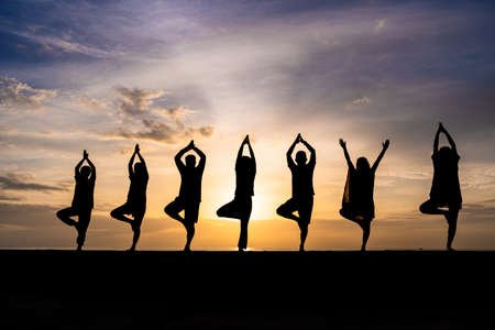 Silhouette of group of people, male and female, doing yoga during colorful sunset or sunrise at a beach, room for copy space Banco de Imagens