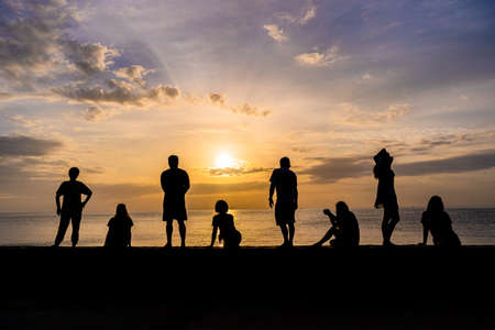 Silhouette of people relaxing watching colorful sunrise at a beach, roof for copy space