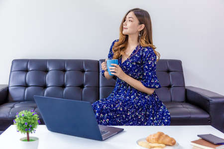 Young beautiful woman in blue dress enjoying her drink while working on her computer in her home living room Banco de Imagens
