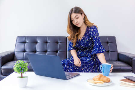 Young beautiful woman in blue dress, picking up coffee cup while working on her computer in her home living room Banco de Imagens