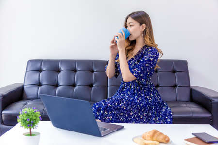 Young beautiful woman in blue dress drinking her coffee during working on her computer in her home living room Banco de Imagens