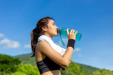 Beautiful young Asian woman exercising in the morning at a running track, taking a rest to drink water