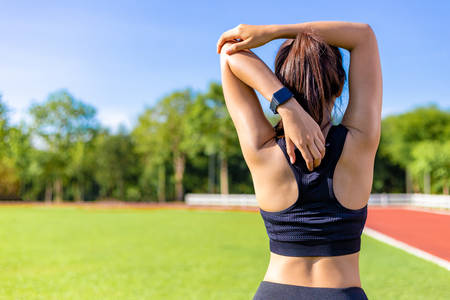 Back view of a beautiful young woman stretching during her exercise in the morning at a running track, clear blue sky with blurred trees in background