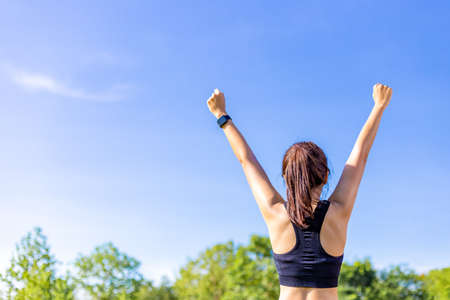 Back view of a woman in stretching up her arms and fists happily at an outdoor field with blurred trees and clear blue sky background on a bright sunny morning, copy space