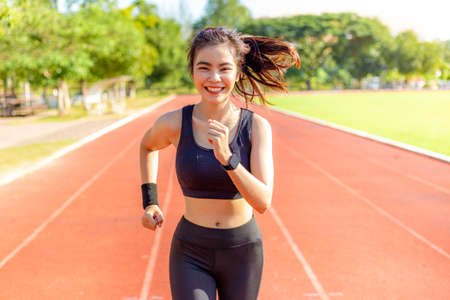 Beautiful happy young Asian woman running for her morning exercise at a running track with blurred track and trees in background, healthy lifestyle