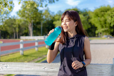 Beautiful happy young Asian woman about to drink her water in the morning at a running track before starting her fitness exercise, healthy lifestyle