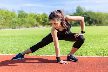 Beautiful young Asian woman stretching before exercising in the morning at a running track, healthy lifestyle Banco de Imagens