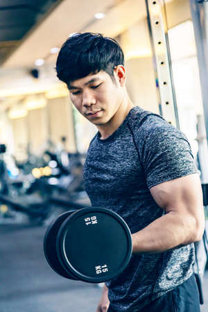 Young Asian man working out lifting heavy dumbbell at a fitness gym, healthy lifestyle