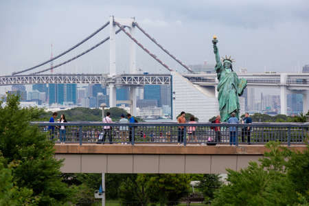 Odaiba, Japan - 18 June 2015 - Tourists visit Odaiba to take picture with statue of liberty and the famous rainbow bridge on June 18, 2015 in Odaiba, Japan
