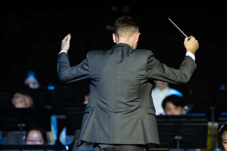 Back view of a male band conductor in formal suit conducting his concert band