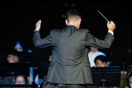 Vue arrière d'un chef d'orchestre masculin en costume formel menant son orchestre de concert