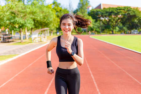 Beautiful young Asian woman running, exercising in the morning at a running track, good healthy lifestyle concept
