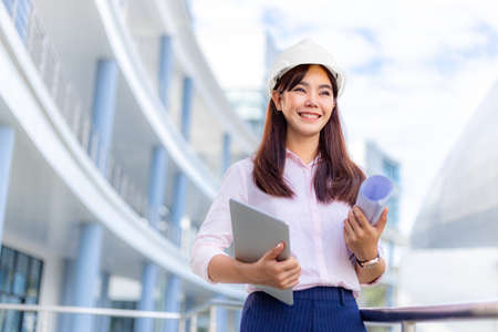 Happy young attractive female Asian engineer wearing hard hat holding her computer tablet and blueprint while standing outside of office building, business construction or engineering concept