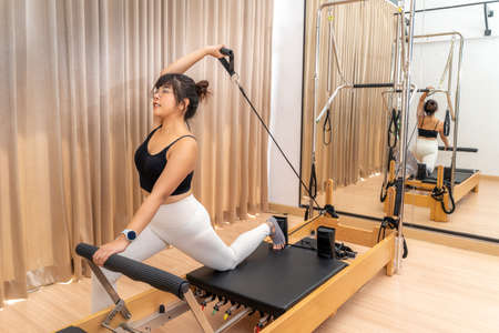Young Asian woman working on pilates reformer machine during her health exercise training