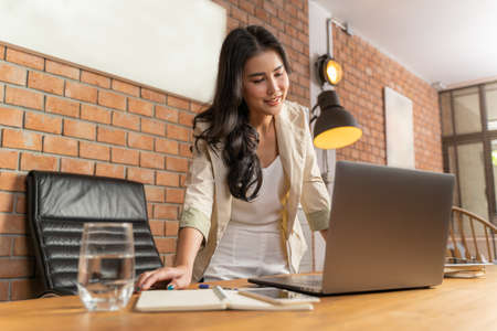 Young beautiful Asian businesswoman standing looking at her computer on her living room's table at her home, work at home concept