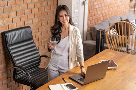 Young beautiful Asian businesswoman standing holding a glass of water and looking at camera during working from home during the COVID lock down