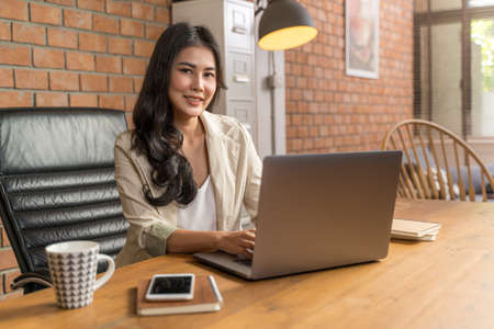 Happy young beautiful Asian business woman smiling at camera while using her computer during working from her home office during COVID pandamic lockdown