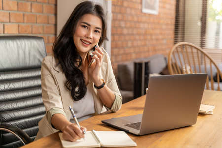 Happy young beautiful Asian business woman taking on the phone while using a computer during working from her home office during COVID pandamic lockdown