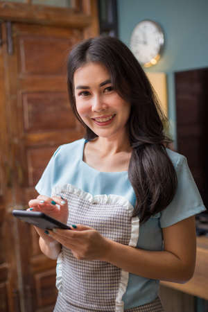 Happy young beautiful Asian woman smiling at camera while holding her phone to check her online messages at her home, modern lifestyle or work from home concept
