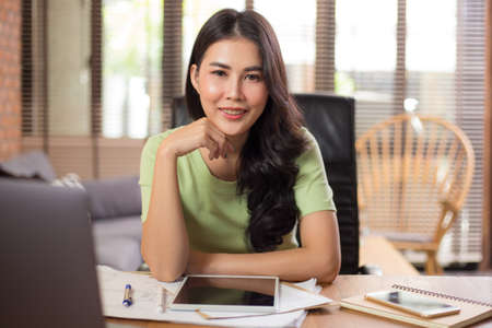 Happy young Asian businesswoman looking staight at camera while sitting and working on her project using her computer and tablet in her living room during work from home