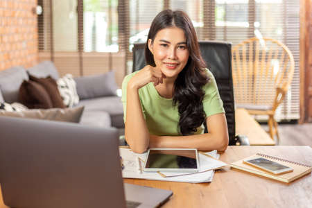 Happy young beautiful Asian woman smiling at camera while taking a break from her work during work from home, business or remote learning concept