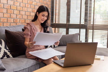 Young beautiful Asian business woman looking at her work plans in front of her laptop computer in her living room while working from home during the COVID lock down