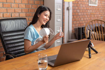 Happy young Asian businesswoman holding N95 face mask and alcohol spray bottle to show her social media fan page about stay safe during COVID lockdown through her online channel on her phone and computer from her living room of her house