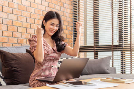 Happy young beautiful successful Asian woman raising up both hand in fists excitedly in front of her computer in her home living room for the success of her business project