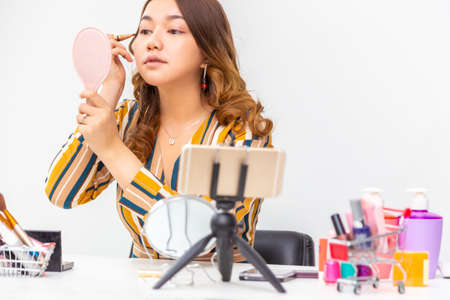 Beautiful young Asian woman, vlogger, putting makeup on while reviewing beauty products on a video blog at home Foto de archivo
