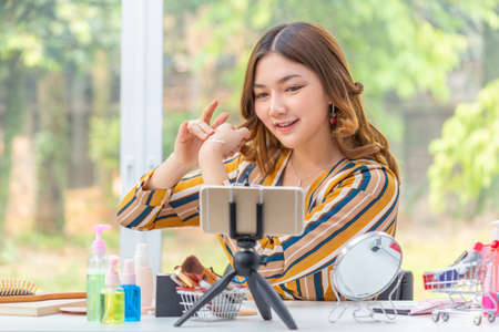 Happy beautiful young Asian woman reviewing beauty products through her online video blog from her home Stok Fotoğraf