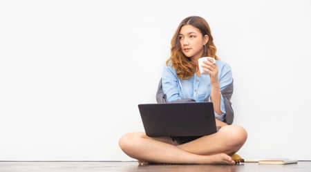 Beautiful young Asian woman sitting on the floor holding a cup of coffee while taking a break from working on her computer at home