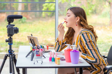 Beautiful young woman putting lipstick make up on her lips while reviewing beauty products on a video blog at home
