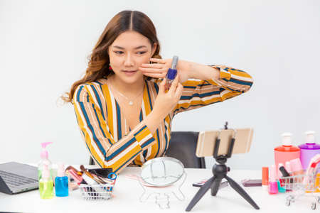 Beautiful young woman showing and reviewing beauty products on a video blog at home Stok Fotoğraf