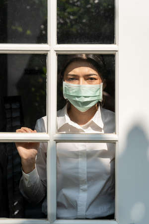 Young woman wearing surgical mask staying inside her home looking out the front door in concern during COVID pandamic lock down