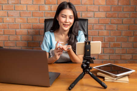 Happy beautiful young Asian woman using hand sanitizer gel on her hands while talking on video call  through the smart phone in her home office, new normal concept